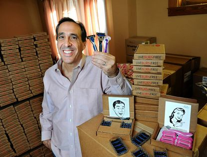 Philip Masiello, president of 800razors.com, is pictured in his home office with the company's razor products.