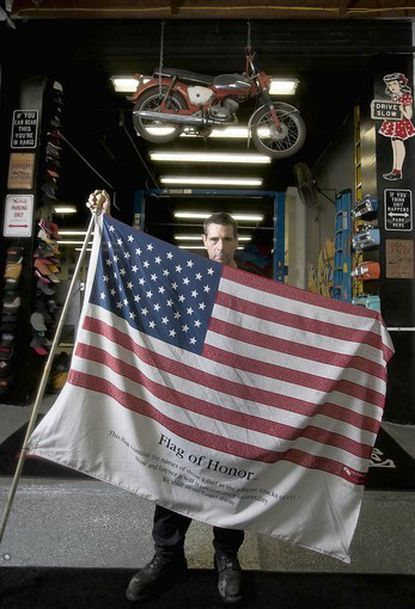 Jeff Millman displays one of his commemorative Sept. 11 flags, the Flag of Honor, at Sisson Street Automotive, his auto repair shop. The flag lists the names of those who perished in the Sept. 11 attacks as of 2003, the year the flag was created.