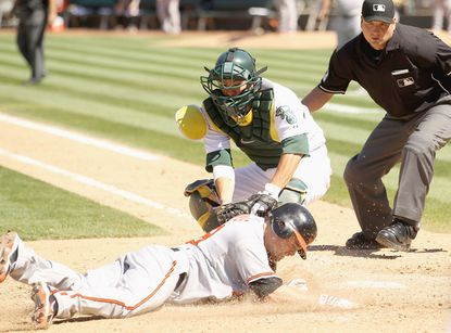 The Orioles' Blake Davis is tagged out by A's catcher Kurt Suzuki for the last out of the game in Oakland, Calif.