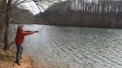 Marvin Mendoza of Owings Mills casts a line into Liberty Reservoir while fishing on its banks Wednesday afternoon.