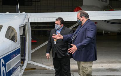 Eric Melancon, (l) chief of staff for the Baltimore Police Department, left and Ross McNutt, founder of the Persistent Surveillance Systems, look over the plane that is helping police to solve crimes.