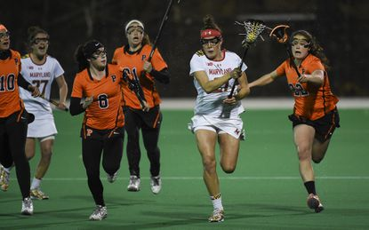 Maryland lacrosse midfielder Taylor Cummings , center, outruns a line of Princeton defenders on April 8 in College Park, Maryland.
