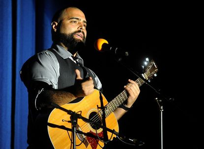 Sal Gonzalez Jr. speaks about his experiences as a wounded veteran during the Concert for Heroes at Liberty High School Saturday.