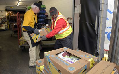 Catonsville MD -- John McMahon, left, Giant store receiver, and Robert L. Jackson, driver for Maryland Food Bank, load Jackson's truck with donated meat from Giant. The Giant grocery store on Wilkens Avenue and others elsewhere donate meat to the Food Bank.