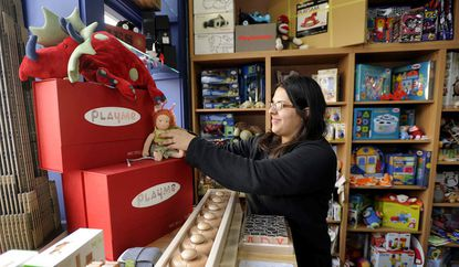 Claudia Towles, owner of aMuse Toys in Fells Point, works on a display of toys at the Baltimore shop.