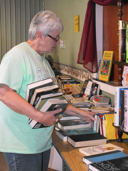 Donna Wright, of Hampstead, a volunteer at the Day of Knowledge Book Fair sponsored by Millers United Methodist Church, sorts and re-organizes books that have been shifted around by those searching through the free volumes during the fair Jan. 17.