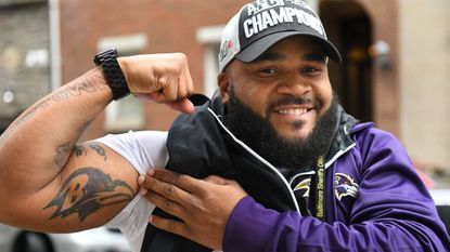 Longtime Ravens fan Hikeen Crampton shows his team spirit downtown Monday after the Ravens clinched the AFC North title Sunday.
