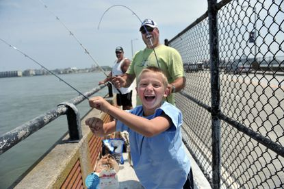 Justin Kula, of Piscataway, N.J., jumps for joy after catching a flounder off the Route 50 bridge. His father, Mike Kula, laughs as he holds his son's rod and reel.