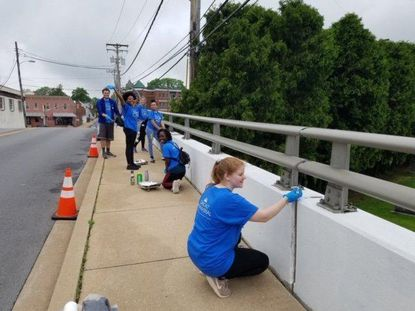 Volunteers from McDaniel College paint an overpass in Westminster as part of the 18th annual Comcast Cares Day. - Original Credit: Courtesy Photo