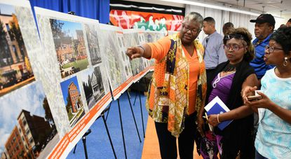 From left: Maxine Mabry, Yvonne Donelson and Diane Russel, who live in the Park Heights community, look at drawings of proposed development in their community. This afternoon at the Langston Hughes Community Center, Baltimore Mayor Jack Young announced that the NHP Foundation and the Henson Development Company have been chosen to develop a 17-acre parcel in the Park Heights community.