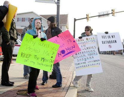 Opponents of a Baltimore County transgender protections bill hold signs in Catonsville in 2012, arguing the bill would make bathrooms unsafe. Opponents of statewide protections for transgender people are using similar arguments as they attempt to put the new legislation to referendum.