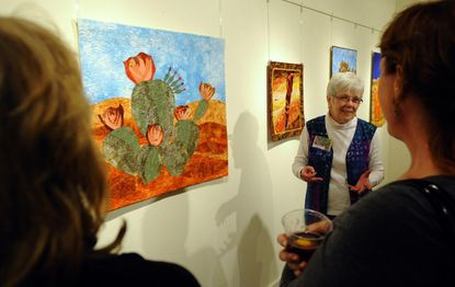 Karen Brown, center, talks about her fiber art with Denise Beaver and Tracy Turner during a reception at the Carroll Arts Center in Westminster Tuesday.