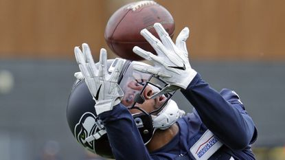 Seattle Seahawks wide receiver Keenan Reynolds, a Naval Academy graduate, reaches for the ball during NFL football practice Tuesday, June 12, 2018, in Renton, Wash. (AP Photo/Elaine Thompson)