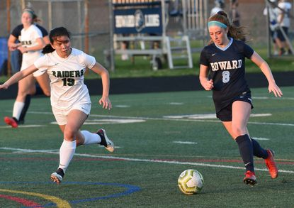 Howard #8, Danielle Campbell advances the ball and scores her 3rd goal of the game, defended by Atholton #19, Amanda Chin. Girls soccer first-round tournament game between Atholton and Howard, Tuesday April 6, 2021 at Howard High School.