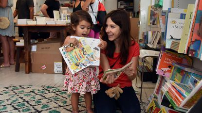 Apolline Salvaggio, 2, looks at books with her mother, Heather Salvaggio, at Greedy Reads, a bookstore in Fells Point.