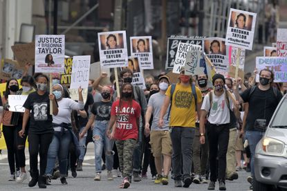 People walk down St Paul Street toward McKeldin Plaza during a march and protest regarding the lack of charges brought against Louisville police in the killing of Breonna Taylor on Sept. 26, 2020. (Karl Merton Ferron/Baltimore Sun Staff)
