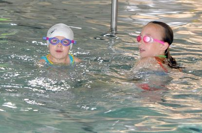 Evie Barczak, left, and her cousin, Eliza, swim at the Ward Family YMCA in Abingdon Thursday, the same day as the 10th anniversary of the opening of the facility.