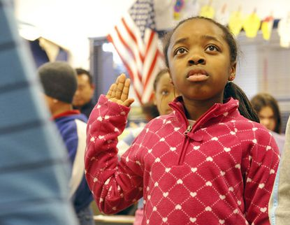At Running Brook Elementary, fourth-grader Tashona Wilson, 9, raises her hand with other classmates as Barack Obama raises his hand on television, and is sworn in as the 44th president of the United States.