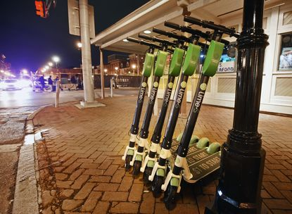 Lime rental scooters parked along Broadway near Aliceanna Street in Fells Point.