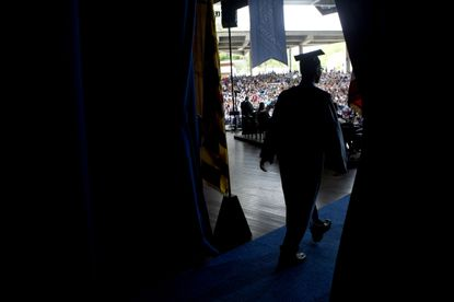 A graduate walks out on the stage to receive his diploma during Reservoir High School's Commencement at Merriweather Post Pavilion in Columbia.