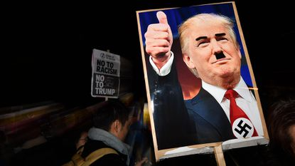 A demonstrator holds a placard showing a picture of U.S. President-elect Donald Trump modified to add a swastika and an Adolf Hitler-style moustache during a protest outside the U.S. Embassy in London on November 9, 2016. File.