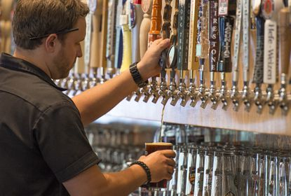 General manager Alex Taylor pours a beer from one of 56 choices at the Frisco Taphouse & Brewery in Columbia.