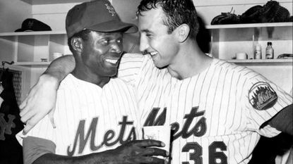 Mets third baseman Ed Charles offers a cool drink to winning pitcher Jerry Koosman after a game against the Cincinnati Reds on July 26, 1968.