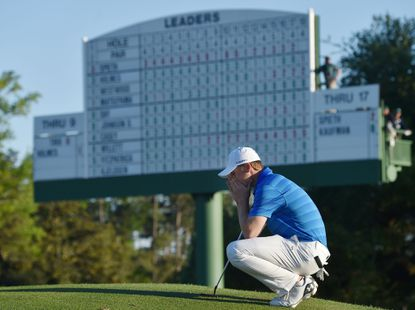 Jordan Spieth gathers his thoughts on the 18th green in front of the leaderboard before finishing his final round of the 80th Masters on Sunday, April 10, 2016, at Augusta National Golf Club in Augusta, Ga.