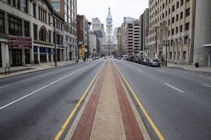 Few people travel on North Broad Street in view of City Hall in Philadelphia, Wednesday, March 25, 2020. Philadelphia Mayor Jim Kenney is issuing a stay-at-home order to the nation's sixth most-populated city to keep its 1.6 million people from leaving home, due to the coronavirus except to get food, seek medical attention, exercise outdoors, go to a job classified as essential or other errands that involve personal and public safety. (AP Photo/Matt Rourke)