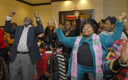 Prince Brooks (left), Sylvia Marion Carley and others cheer in a meeting room at the JW Marriott in Washington as Barack Obama is sworn in as the 44th president.