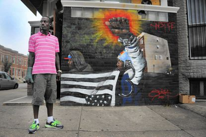 Standing on North Avenue at Mount Street, resident Tayvon Wiggins talks about his perception of alleged arrests targeting low-income residents for minor offenses by the Baltimore Police.