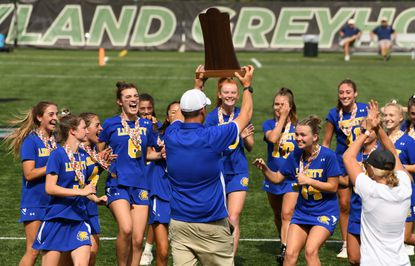 Liberty head coach Tom Brandel presents the championship trophy to his players as they celebrate following their win over Fallston during the Class 1A girls lacrosse championship game at Loyola University's Ridley Athletic Complex on Friday, June 18, 2021.