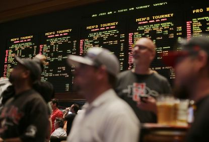 In this file photo, NCAA basketball tournament games are displayed on a board at the Mirage hotel-casino Race & Sports Book in Las Vegas. Maryland is inching closer to legalizing sports betting.