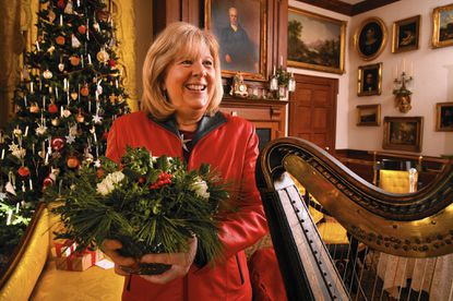 Claire Jones, a landscape designer, in the music room of the Hampton Mansion, with a small tabletop arrangement made by garden club members. Jones was selected to decorate the White House this holiday season.