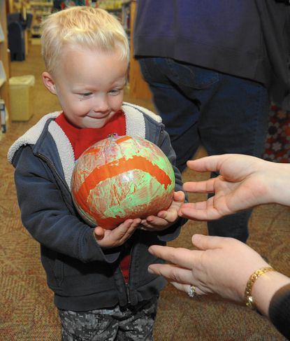 """Gavin Andrews, 2, of Eldersburg, has a decorated pumpkin to deliver to the Eldersburg Public Library for the library's """"Pumpkin Patch"""" program that is open to all. A drawing will be held after Halloween."""