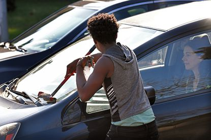 A squeegee kids washes a windshield at the I-83 exit on North Avenue in Baltimore.