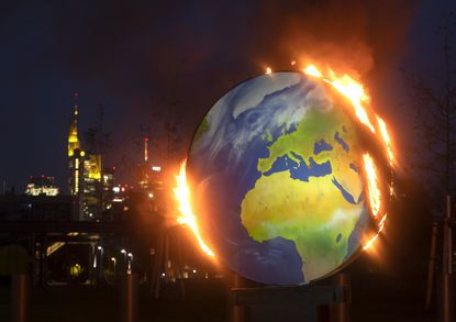 "A makeshift globe burns in front of the European Central Bank in Frankfurt, Germany on Oct. 21, 2020. Activists of the so-called ""KoalaKollektiv"", an organization asking for climate justice, protested with the burning of the globe against the ECB's climate policy."