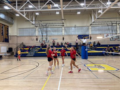 Dulaney junior Charlie Vail, right, celebrates with her teammates after the Lions victory in four sets over Catonsville.