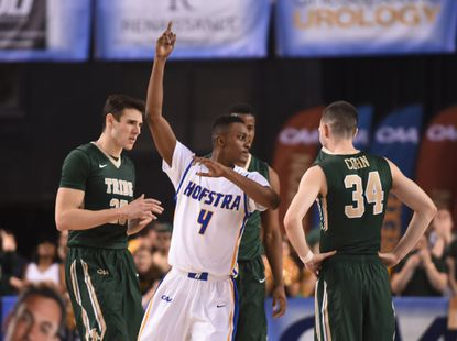 Hofstra's Desure Buie celebrates in front of William & Mary's Terry Tarpey, Daniel Dixon and David Cohn at the end of the game.