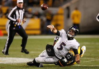 Joe Flacco throws the ball away while being dragged down by James Harrison on Sunday night.