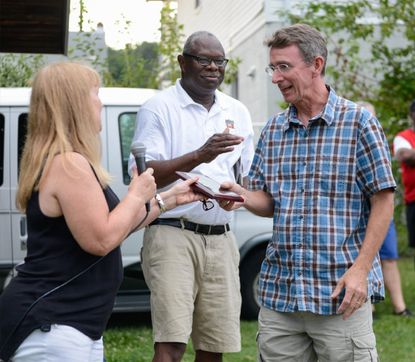 Michael McAuliffe, right, receives a Community Leadership Award from Carol Mox, then president of the Halethorpe Improvement Association, and Otis Collins of the Halethorpe Civic League Association, on Aug. 1, 2017.