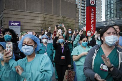 In this April 28, 2020, file photo medical personnel attend a daily 7 p.m. applause in their honor, during the coronavirus pandemic outside NYU Langone Medical Center in the Manhattan borough of New York. Such selfless behavior needs to be more widespread as experts point out that 70,000 U.S. lives might be spared between now and year's end if Americans consistently wore masks. (AP Photo/John Minchillo, File)