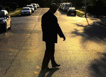 Baltimore Police Commissioner Anthony W. Batts is silhouetted during his walk around a west Baltimore block.
