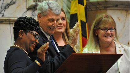 Speaker Pro Tem Adrienne A. Jones, left, swears in House Speaker Michael Busch, as his daughter Erin and wife Cindy, far right, look on during the opening day of the 2017 Maryland General Assembly session.